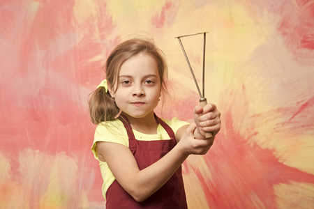 Chef child with masher for potato. Kid in cook apron. Cooking with kitchen tool. Childhood and education. Small girl on colorful background.