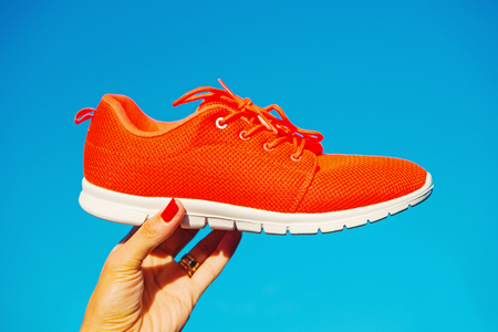 Sports shoes sneakers on blue sky background. Sports in the open air. woman hand holding orange sneakers fitness and health