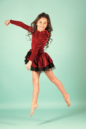 Little girl dancer jump on blue background. Child dance in red dress barefoot. Happy childhood concept. Performance, ballet, gymnastics, activity, energy. Grace, beauty, fashion. Punchy pastel trend Archivio Fotografico