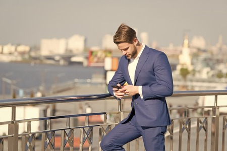 Businessman with smartphone on terrace on cityscape, business communication. Man in business suit with mobile phone, new technology. Business communication, new technology, sms. Modern life, lifestyle