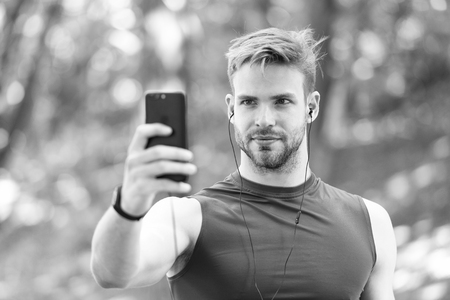 Sport gadget concept. Athlete mobile phone set up playlist before runnig. Man athlete busy face setting up smartphone app, nature background. Sportsman training with pedometer and earphones.