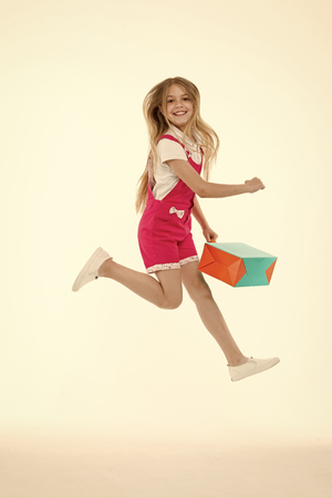 Happy girl jump with shopping bag isolated on white. Little child smile with paper bag. Kid shopper in fashion jumpsuit. Holidays preparation and celebration. Great day for shopping at black friday.
