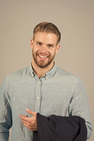 Man smile with bearded face and blond hair, haircut. Macho happy smiling in blue fashionable shirt, fashion. Mens fashion, style and trend. Grooming and hair care in beauty salon, barbershop