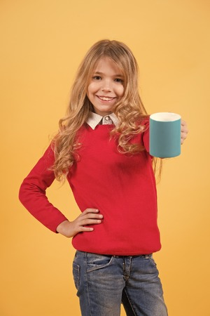Thirst, dehydration concept. Child smile with blue cup on orange background. Tea or coffee break. Girl with long blond hair in red sweater hold mug. Health and healthy drink. Banque d'images