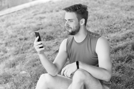 Sport gadget concept. Athlete with fitness tracker or pedometer. Man athlete on busy face setting up fitness tracker with smartphone app, nature background. Sportsman training with pedometer gadget.