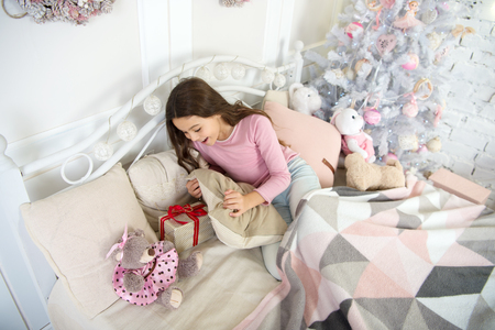 delivery christmas gifts. happy new year. happy little girl celebrate winter holiday. sleeping and dreaming. christmas time. morning before Xmas. little child girl with xmas present. home interior.