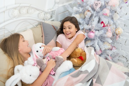 Jolly and funny. Little children enjoy Christmas. Little children have Christmas fun. Small girls fight over toys. Active small kids in bed at Christmas tree. Childhood games on xmas and new year. 스톡 콘텐츠