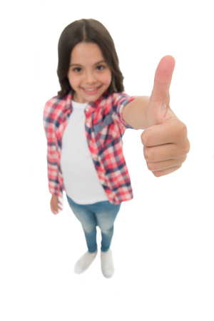 Kid girl long curly hair posing confidently. Girl smiling face feels confident. Child confidently showing thumbs up. Upbringing confidence concept. Feel so confident with parental support. I like it. Stock Photo