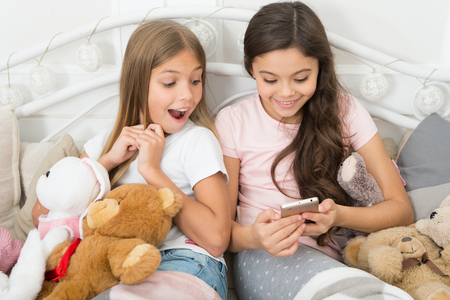 Message from Santa. Little girls use smartphone in bed. Happy little children with mobile phone. Ordering gifts for Christmas and New Year by phone. Merry Christmas and Happy New Year greetings.