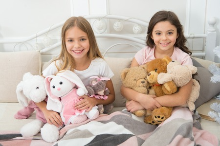 Best time together. Small children have Christmas fun. Little girls play with toys. Happy kids in bed at Christmas tree. Small children enjoy Christmas. Childhood games on xmas and new year.