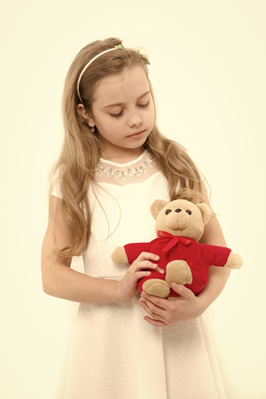 Child with teddy bear isolated on white. Girl play with soft toy. Birthday, anniversary celebration. Happy childhood concept. Holiday present and gift