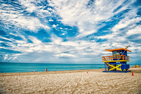 Lifeguard tower for rescue baywatch on south beach in Miami, USA. Red and blue wooden house on sea shore on cloudy sky background. Summer vacation and resort. Public guarding and safety concept Stock Photo