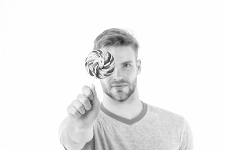 Man hold big sweet lollipop in front of his face. Man bearded likes sweets. Guy offers giant lollipop candy. Lollipop lick one of great oral techniques you can master. Would you like to lick lollipop. 版權商用圖片