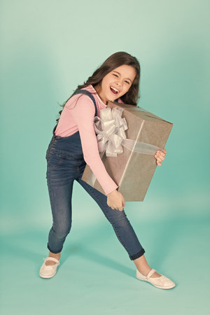 Fabulous little girl carrying gifts on turquoise background.
