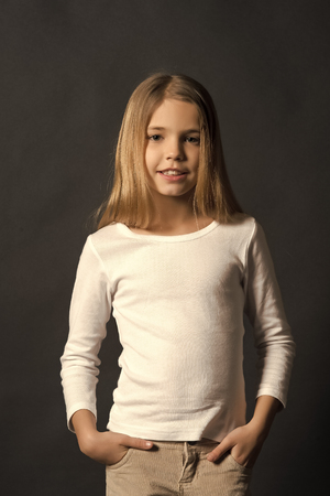Child model with long hair in white shirt pose on black background. Beauty, fashion, look concept