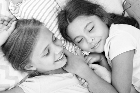 Pleasant dream on her mind. Girls fall asleep after pajamas party in bedroom. Girls have healthy sleep. Children relax on bed. Sleepy kids in pajamas having rest on comfortable bed. Happy childhood. Banque d'images