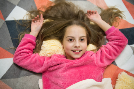 Good morning. I want to play. International childrens day. Childhood happiness. Small girl child ready to sleep. Time to relax. Little happy girl in bedroom. Pajama party. Good night. Imagens