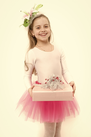 Holiday, birthday, anniversary celebration. Child with flower in long blond hair isolated on white. Present or gift giving. Girl ballerina smile with box in pink skirt tutu. Boxing day concept.