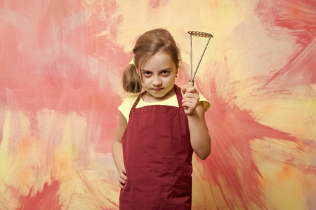 Girl cook with metal potato masher in red chef apron posing on colorful abstract wall. Cooking utensils concept. Child and childhood Stock fotó
