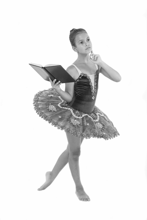 Girl ballerina dancing while read book. Ballet career issues. Depriving children ballerina. Most of time child dancer spend in gym training and practicing performance. No time for school studying.