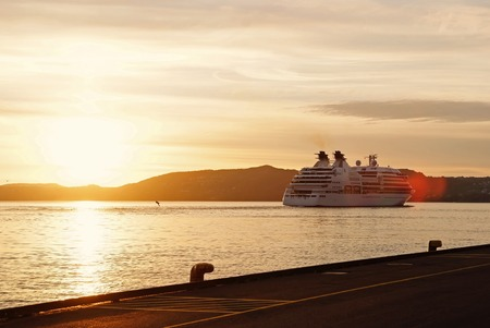 Passenger ship or ferry boat in sunset sea in Bergen, Norway. Cruise, journey, trip, wanderlust, vacation concept.