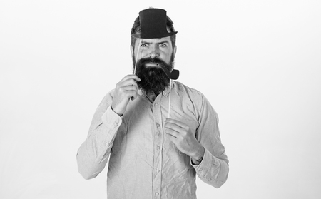 Guy smokes tobacco pipe. Hipster with beard and mustache on serious face posing with photo booth props. Aristocracy concept. Man holding paper party props tobacco pipe and top hat, white background.