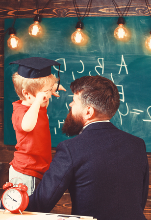 Man turned back embracing blond boy in graduation cap. Tired kid rubbing his eyes. Adult and child in study room. Stockfoto