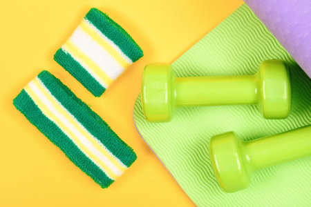 Dumbbells made of plastic on wavy green and yellow background. Sports and healthy lifestyle concept. Barbells in small size and hand band on purple yoga mat, top view. Shaping and fitness equipment