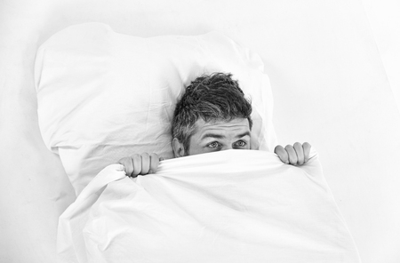 Sleepyhead concept. Guy hides face under blanket. Man with surprised face lies on pillow under blanket. Man wants to stay in bed, white background, top view, close up.