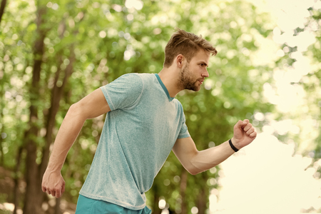 Moving to his goal. Man confident young running in park, side view. Sportsman ambitiously moves to achieve sport goal. Masculinity and sport achievements concept. Guy concentrated runs for his goal. Stock Photo