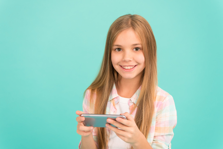 Problem of youth. Mobile phone and internet addiction. Addicted to internet online games. Mobile gadget dependence. Girl small child smiling hold smartphone. Internet surfing and social networks.