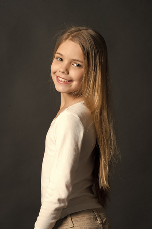 Happy child, childhood concept. Girl with smile on cute face on dark background. Youth, skincare, health. Kid model smiling with long healthy hair. Beauty, look, hairstyle. Stockfoto