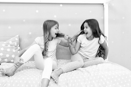 Happy childhood moments. Kids girls sisters best friends full of energy in cheerful mood. Grow strong and healthy hair. Hair care concept. Strong hair. Children cheerful play with hair in bedroom.