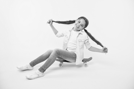 Girl show long ponytail hairstyle sit penny board yellow background. Child cute hairstyle ride penny board. Proud of long hair. Hairstyle for active leisure. Keep hairstyle tidy during sport activity. Banque d'images - 117460428