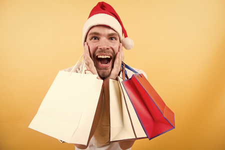 Man in santa hat with bags on orange background. Winter sale, shopping concept. Macho shopper with surprised face hold paperbags. Happy holidays celebration.