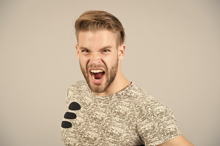 Man shout angry in tshirt on grey background. Grooming, male beauty concept. Fashion, style, trend. Barber salon, barbershop. Macho with bearded face and stylish hair, haircut, copy space
