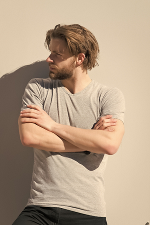 Man in t shirt pose with folded hands on grey wall. Macho with beard and blond hair on sunny day. Grooming, male beauty. Fashion, style concept. Barber salon, barbershop.