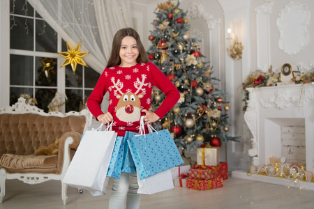 small happy girl at christmas. Christmas. Kid enjoy the holiday. The morning before Xmas. girl with shopping bags. New year holiday. little child girl likes xmas present. Happy new year.