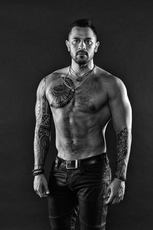 Man brutal unshaven hispanic appearance tattooed arms. Bearded man show tattooed torso. Brutal strict macho with tattoos. Masculinity and brutality. Tattoo culture concept. Tattoo brutal attribute.