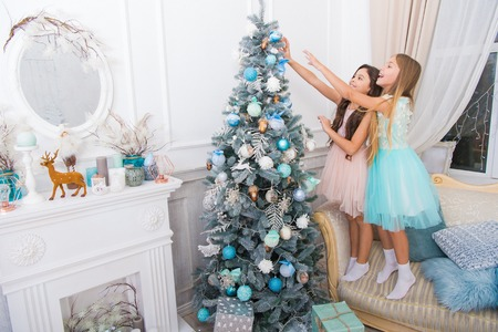delivery christmas gifts. happy little girls sisters celebrate winter holiday. christmas time. happy new year. little children girl with xmas present. Family holiday. decorate christmas tree. Look.