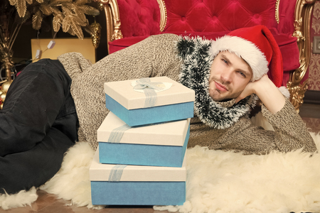 Macho in santa hat with present boxes relax on furry carpet. Man ready to celebrate party. New year, xmas, eve. Winter holidays celebration. Boxing day concept