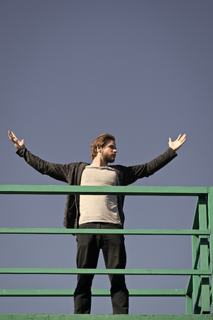 Man with open hand gesture stand on height on sunny blue sky. Freedom, success concept