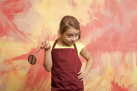 Small girl on colorful background. Chef child with masher for potato. Kid in cook apron. Childhood and education. Cooking with kitchen tool.