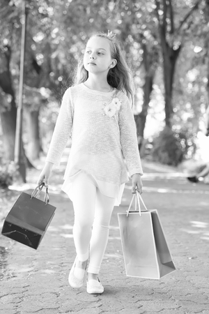 Child with paper bags in summer. Girl with shopping bags walk in park. Little princess with crown on long blond hair. Shopping on sale and purchase. Kid shopper in fashion clothes outdoor.
