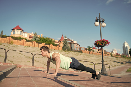 Macho doing pushups on red brick stairs outdoors. Man with muscular hands, biceps, triceps, strong muscles. Athlete in tracksuit on sunny summer day. Workout and training. Healthy lifestyle concept. 写真素材