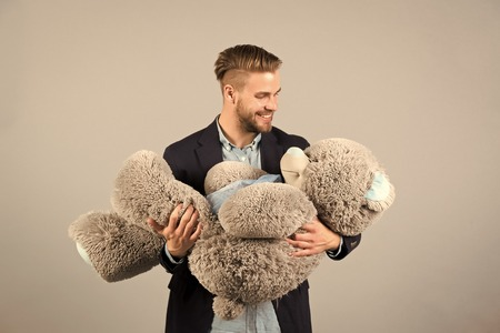 Man hold big teddy bear soft toy as present for birthday party on grey background. valentines day