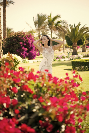 Woman pose with blossoming flowers. Fashion model with brunette hair in garden. Beauty girl with makeup and glamour look. Sensual bride in white dress on summer day. Wedding and womens day celebration