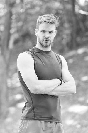 Sportsman with arms crossed in summer park. Strong man ready for training on fresh air. Fit and confident macho. Sport and workout activity. Relax in forest or park. Wellness and bodycare. 写真素材