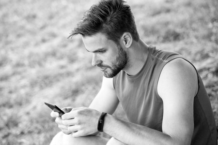 Stay online and available. Sportsman text sms on fresh air. Man relax with smartphone on green grass. Summer activity. Always in touch. Technologies make training easier. Sport blog and weblog. Imagens