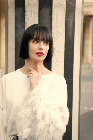 Girl with brunette hair hairstyle in paris, france. Woman with red lips, makeup face at striped column. Beauty and hairdressing salon. Look, visage, make up. Fashion, style concept.